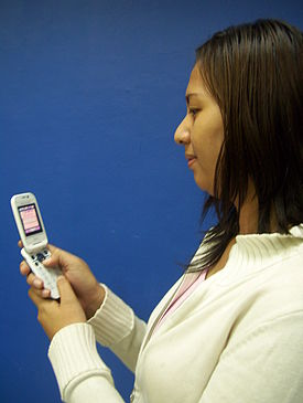 A woman using a cell phone.