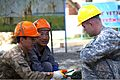 Mongolian Armed Forces Sgt. Gantugs Battsengel, left, a builder with the 017 Construction Unit, hands wire cutters to U.S. Army Sgt. Sean Belka, an engineer with the 176th Engineer Company, 96th Troop Command 130720-M-MG222-002.jpg
