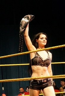 A Caucasian female wrestler with black hair and pale skin wearing various wrestling attires, while raising a championship belt on her right hand inside a wrestling ring.