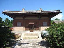 The Great Buddha Hall of Nanchan Temple. A small timber building with massive overhanging eaves with a bright blue sky behind it.