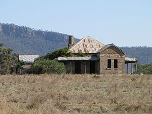 Nangar National Park - An abandoned homestead at Murga in front of the cliffs of Nangar National Park, as seen from the Escort Way