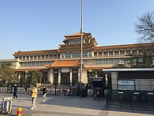 An ornate building front stretching the width of the image, slightly tilted, against a uniformly blue sky. Its front has a projecting pavilion in the Chinese style, echoed by a similar pagoda-style top on the roof above it.