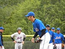 A man in a blue baseball jersey and baseball cap and white baseball pants bending over from the waist; he wears a black baseball glove on his left hand