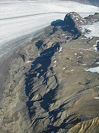 Dark rough rock explosed near a glacier.