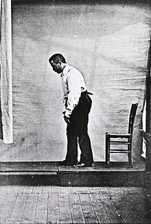 Black and white picture of male with PD stooping forward as he walks. He is viewed from the left side and there is a chair behind him.