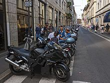A row of black motorcycles parked in the foreground alongside a narrow street that recedes to near the background. Several men are sitting around and talking on some of the motorcycles, and people walk on the sidewalks on both sides of the street