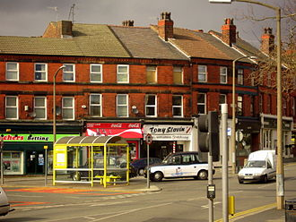 "Penny Lane - Tony Slavin (the white building on the corner) occupies the location of the original Bioletti's barbershop mentioned in the song as ""a barber showing photographs / of every head he's had the pleasure to know""."