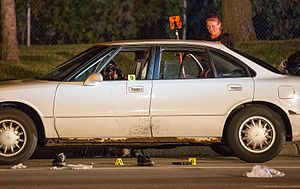 Shooting of Philando Castile - Shoes and a gun on the ground outside Philando Castile's blood-stained car as Minnesota Bureau of Criminal Apprehension (BCA) investigators take photographs of the scene
