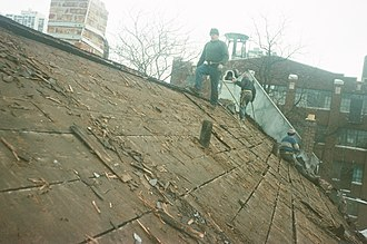 Roofer - Roofers on a pitched roof in the United States conducting a roof tear-off