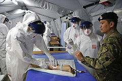 Practising taking blood in Ebola saftey suits (15649429018).jpg