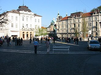 Prešeren Square - A view of the square from the end of Čop Street (2005). The Prešeren Monument stands at the eastern side of the square. There are three birches behind it. The building to the left is the Central Pharmacy. In the back, the Ljubljanica flows past the square.