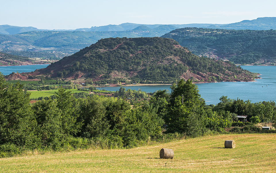"""The Presque-isle of Rouens (253m) and the Salagou Lake (""""Lac du Salagou"""") in the commune of Clermont-l'Hérault.  The Salagou Lake is an artificial lake dating from the beginning of 1969. The hill has a red aspect because it is constituted by ruffes, a local name indicating the red lands formed by detrital sedimentary rocks. Photo taken from the South in  the commune of Liausson. Hérault, France."""