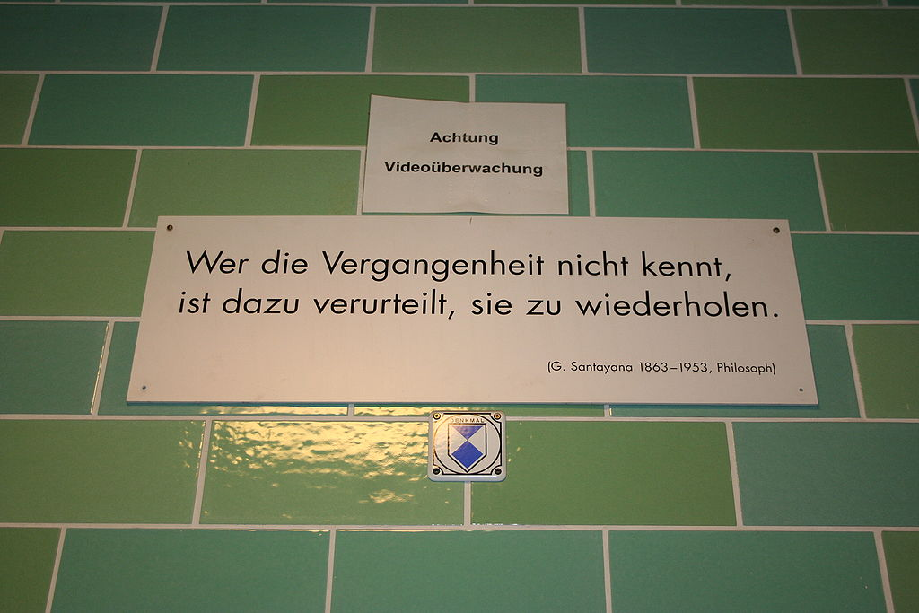 """A green brick wall with a white sign reading """"Wer die Vergangenheit nicht kennt, / ist dazu verurteilt, sie zu wiederholden. / (G. Santayana 1863–1953, Philosoph)"""