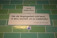 """Een groene bakstenen muur met een wit bord met de tekst """"Wer die Vergangenheit nicht kennt, / ist dazu verurteilt, sie zu wiederholden. / (G. Santayana 1863–1953, Philosoph)"""