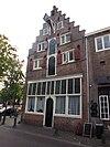 foto van Hoek Lieve Vrouwekerkhof. PAKHUIS met trapgevel, vensterbogen met metselmozaïek gevuld, uitstekende hijsbalk