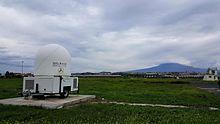 Radar di monitoraggio delle ceneri vulcaniche dell'Etna (sullo sfondo), installato all'Aeroporto di Catania-Fontanarossa dalla Protezione Civile.