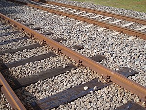 Railroad tie - Wooden ties are used on many traditional railways. In the background is a track with concrete ties.