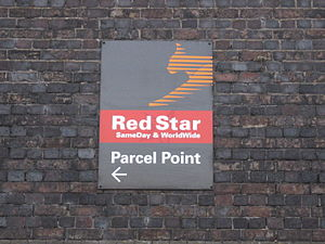 "Red Star Parcels - Red Star Parcels sign at Reading railway station, England, photographed in 2009.   Note ""Lynx"" logo"