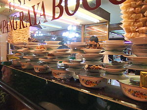Padang cuisine - An array of Padang dishes arranged in a restaurant window.