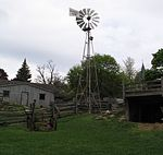 View of a wind wheel near two 19th century wooden structures at Riverdale Farm
