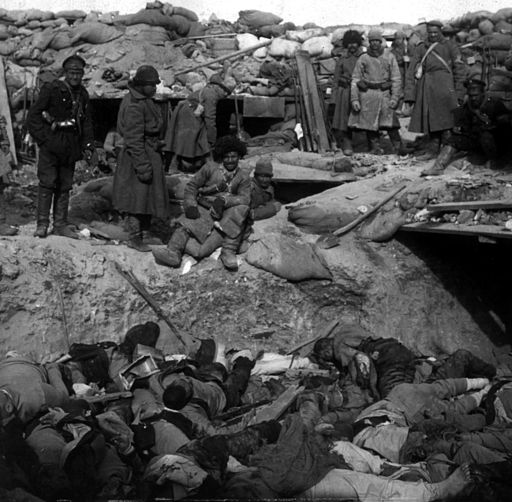 Russian soldiers stand over trench of dead Japanese