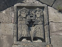 Two bearded figures in stone relief, holding an object that looks like an open door with a bell on top.