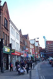A row of shops facing onto a very busy pavement. A large six-storey brick building is visible in the background