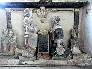 Sir John Northcote, 1st Baronet - Effigies of Sir John Northcote, 1st Baronet (1599-1676) and his wife Grace Halswell (d.1675). Detail from base of monument to his father John Northcote (1570-1632), Newton St Cyres Church. On a cartouche above are shown the arms of Northcote impaling Azure, three bars wavy argent overall a bend gules (Halswell). Their sons are shown kneeling behind their father and their daughters behind their mother. the effigies of some infants of both genders lie on the floor in swaddling clothes