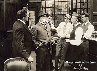 George Fawcett - In a still from The Corner (1916), millionaire David Waltham (played by George Fawcett, holding a cigar and scowling) stands in a group of businessmen.