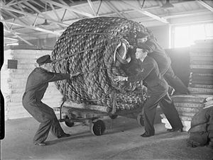 Hawser - Supply ratings handling a coil of 16 inch towing hawser (rope) at the Royal Navy's Naval Stores Department, Nore, Harwich, which supplies all sea-going ships with the stores and provisions that they need. Note that the coil is bigger than the men and they need a trolley to transport it.
