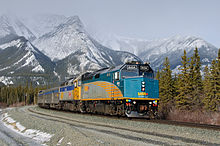 Passenger train rounding a bend, with snow-capped mountains in background