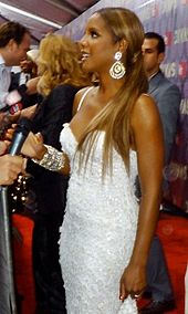 Photograph of a woman being interviewed by a reporter. She has long blond hair that is combed with a pony tail. The woman wears a long white dress, which has diamonds throughout. Accessories she wears are diamond bracelets, a ring and earrings.