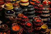 An image showing a number of pots which are made traditionally, black coloured with red and green work on it.