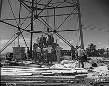 Mænd står omkring en stor olierig-type struktur.  En stor rund genstand hejses op.