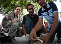 U.S. Army Maj. Kate Flocke, left, a medical team lead, evaluates Philippine health workers Renon Paulo, center, and Ray Grogoro as they simulate placing an IV in the arm of a mock burn victim during a mass 130405-N-VN372-260.jpg