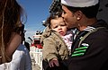 US Navy 040229-N-3642E-011 Aviation Boatswain's Mate (Equipment) Airman Ulysses Hernadez kisses his daughter after returning from a six-month deployment aboard the nuclear powered aircraft carrier USS Enterprise (CVN 65).jpg