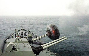 US Navy 040703-N-1464F-001 The Peruvian cruiser Almirante Grau CLM-81 fires one of its 15.2 cm caliber cannons.jpg