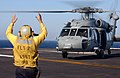 US Navy 040710-N-4757S-010 Aviation Boatswain's Mate 3rd Class Dustin Shipman signals to an MH-60S Nighthawk helicopter assigned to the Chargers of Helicopter Cargo Squadron Six (HC-6) during a vertical replenishment on the fli.jpg