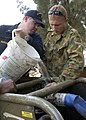 US Navy 050108-N-6736W-002 Lt.j.g Brad Dandurano, left, of Klamath Falls, Ore., assists Australian Army Pvt. Chris Brundon in purging a water pump in an attempt to get fresh water flowing into much needed areas destroyed by the.jpg
