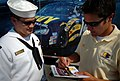 US Navy 050909-N-9769P-165 Aviation Boatswains Mate 2nd Class Elias Rodriguez receives an autograph from the No.14 Navy Dodge Charger NASCAR driver David Stremme.jpg
