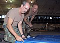 US Navy 071023-N-5366K-017 Chief Utilitiesman John L. Thomason and Chief Builder Tor E. Letterman prepare a tarp to be used as a makeshift partition at Special Boat Team 12's Mark V boat hanger at Naval Air Station North Island.jpg