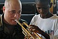 US Navy 090324-N-1688B-239 Musician 1st Class Justin Benge, embarked aboard the amphibious transport dock ship USS Nashville (LPD 13), plays a trumpet with the help of a student from Pacelli School of the Blind in Lagos Nigeria.jpg