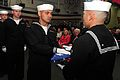 US Navy 110401-N-KD852-536 Culinary Specialist 3rd Class Phillip Cotoio passes the national ensign to Logistics Specialist 2nd Class Marcusallen Bu.jpg