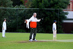 Wide (cricket) - An umpire signals a wide in a junior cricket match.