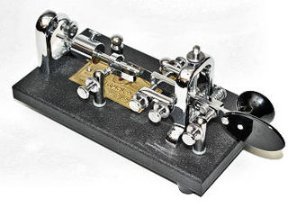 "Vibroplex brand semiautomatic key (generically called a ""bug""). The paddle, when pressed to the right by the thumb, generates a series of dits, the length and timing of which are controlled by a sliding weight toward the rear of the unit. When pressed to the left by the knuckle of the index finger, the paddle generates a single dah, the length of which is controlled by the operator. Multiple dahs require multiple presses. Left-handed operators use a key built as a mirror image of this one. VibroplexBug.jpg"