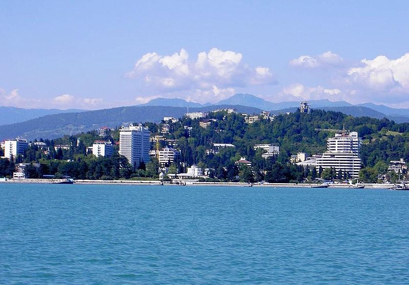 A view of Sochi, Russia from the Black Sea. Image shows a strip of sea, then the city rising up a hill from the water's edge, the buildings nearly lost in lush green vegetation. The Caucasus Mountains rise in the background behind the city. Public domain image courtesy Ojj! 600 via Wikimedia Commons.