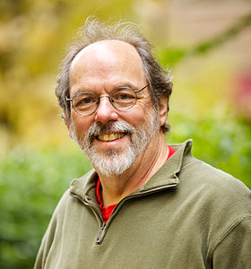 A bearded man in his early sixties grinning while wearing eyeglasses and a fleece jacket