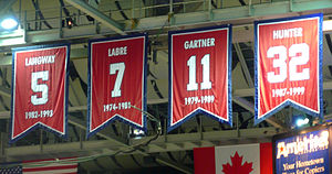 Four red banners with large numbers hang from the ceiling of an arena