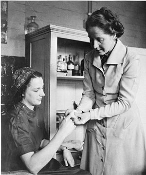First aid room - A female worker receives first aid for a sore finger from her supervisor in a medical room, circa 1941