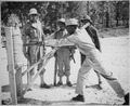"""Lt. B. Holmes instructing cadres in the art of parry and long thrust in bayonet practice. Left to right, T-Sgt. Leroy S - NARA - 531140.tif"